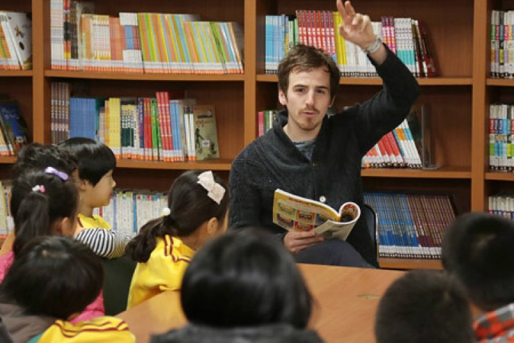 A native English teacher reads to students in his classroom at Myongwon Elementary School in Seoul in this photo taken in April 2013. / Korea Times file