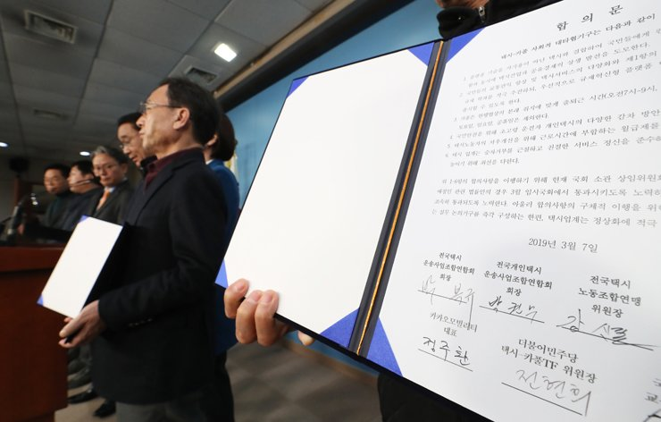 The special consultation committee comprised of representatives from the ruling Democratic Party of Korea, the taxi industry and Kakao Mobility present their agreement at the National Assembly, Thursday, after months of deadlock over allowing paid ridesharing services to operate in Korea. Yonhap