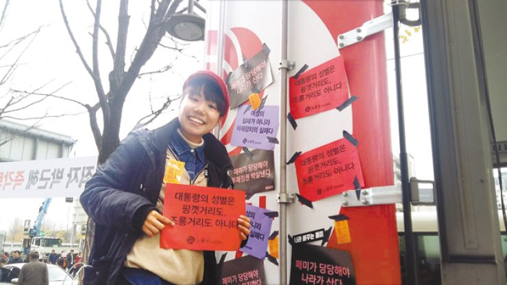 An activist holds a poster reading 'The President's gender is neither a matter of excuse, nor a matter of mockery,' at a rally in Seoul calling for President Park Geun-hye's resignation over her involvement in an influence-peddling scandal, Nov. 19. / Courtesy of Feminists Committee of Labor Party