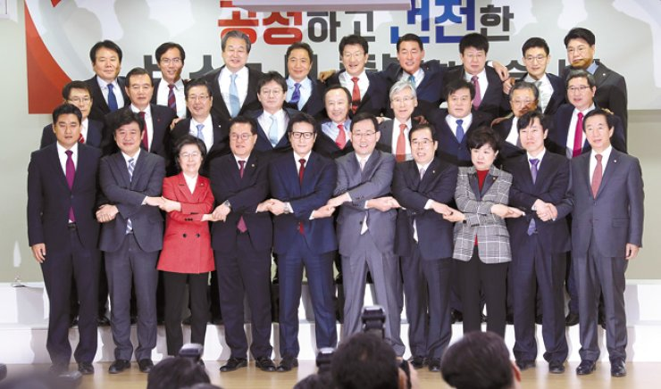A group of 29 lawmakers pose at the National Assembly, Tuesday, after leaving the ruling Saenuri Party to create a new conservative party. They automatically gained the status of a National Assembly negotiating group prior to the official launch of the party next month. / Yonhap