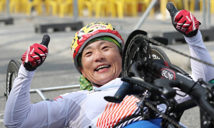 Cyclist Lee Do-yeon raises her hands after winning a silver medal in the women's individual cycling road event in the H1-2-3-4 classification on Friday afternoon (local time). / Yonhap