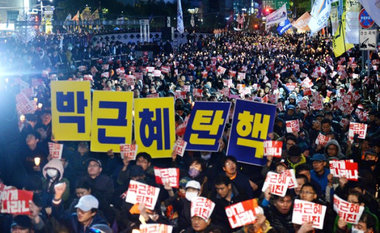 Protesters hold signs that read 'Park Geun-hye resign' during an anti-president rally at Cheonggye Plaza in Seoul, Saturday evening. An anti-Park protest will be staged every 7 p.m. at the venue from Tuesday until Nov. 12. / Yonhap