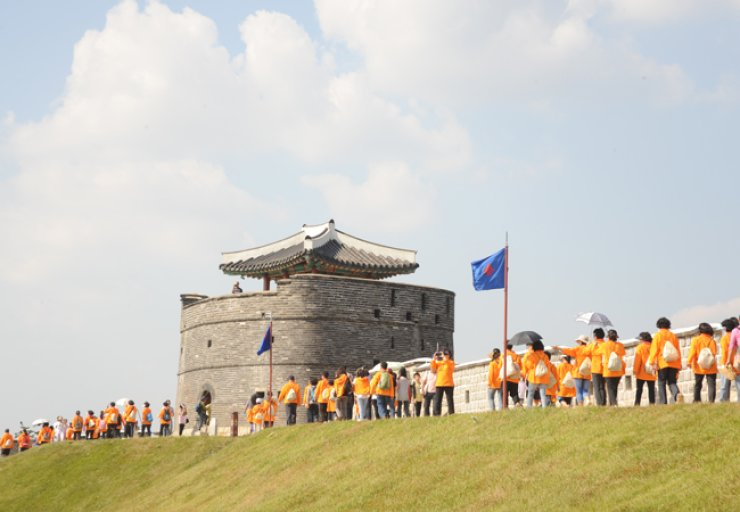 People walk along the walls of Hwaseong Fortress in this file photo. / Courtesy of Suwon City