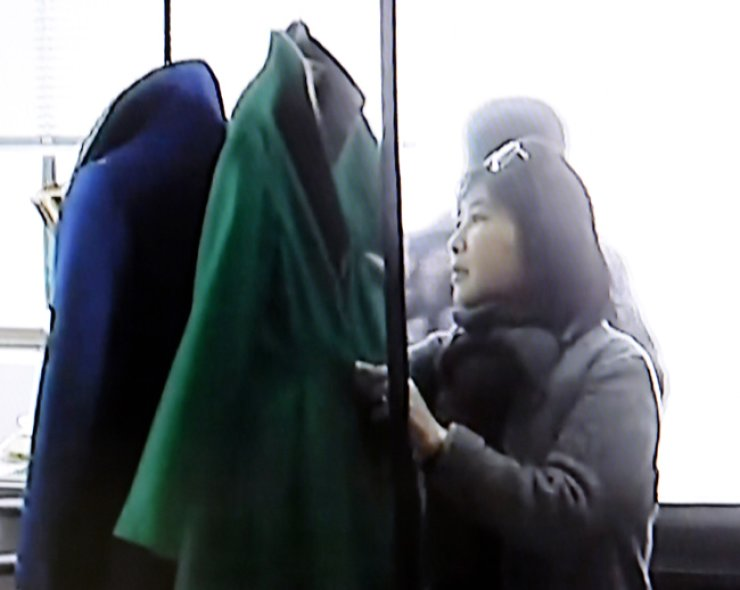 Choi Soon-sil looks at clothes in a Seoul dress shop in this photo captured from cable network TV Chosun. Choi is believed to have chosen what President Park Geun-hye wore at major meetings. / Korea Times File
