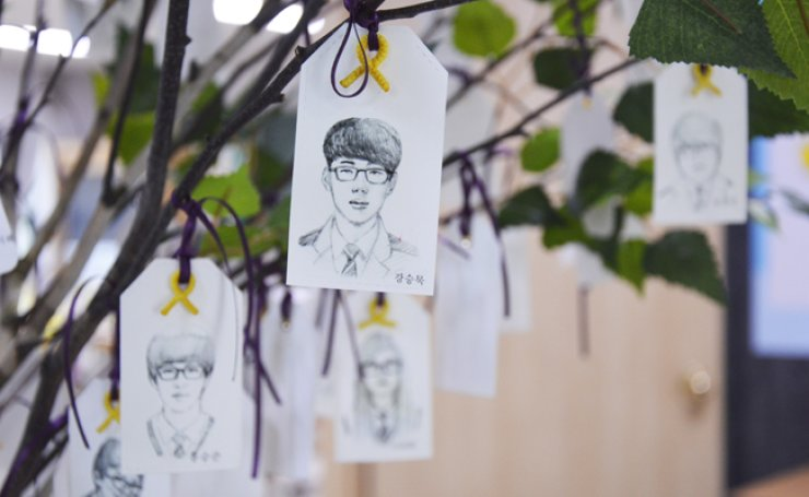 Caricatures of the 250 victims hang in a tree with yellow ribbons ― a symbol commemorating those who died in the Sewol ferry disaster ― attached to each student's picture to honor them. / Korea Times photo by Hong Dam-young
