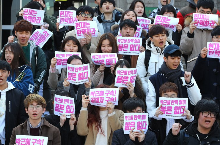 Students hold signs that read 'Arrest Park Geun-hye' and 'No spring without Park Geun-hye's impeachment' at Dongguk University in Seoul, Thursday, on the eve of a historic Constitutional Court impeachment ruling on whether to remove or reinstate Park as president. / Yonhap