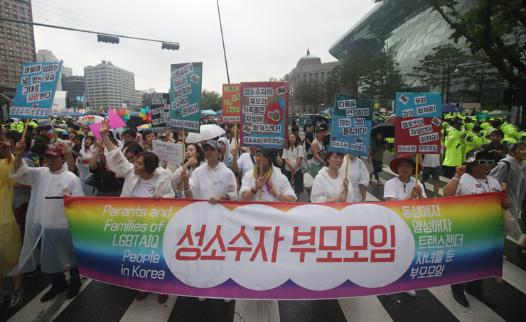 Participants of the Korea Queer Culture Festival march along Sejong-daero Road between Seoul City Hall and Gwanghwamun Square. / YonhapParents of sexual minorities carry a banner proclaiming themselves as 'the association of parents of homosexual, bisexuals and transgender children' in the festival. / YonhapForeign members of the festival drape themselves in rainbow flags, the festival's symbol, in front of Seoul City Hall on July 15. / Yonhap