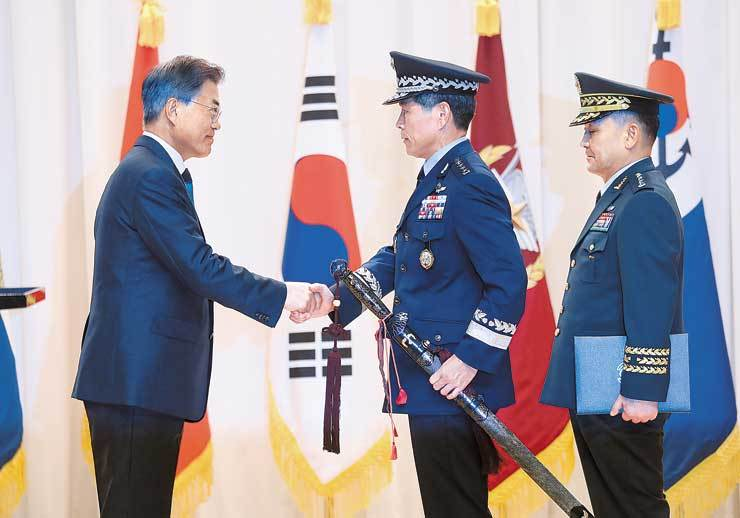 President Moon Jae-in shakes hands with new Joint Chiefs of Staff Chairman Gen. Jeong Kyeong-doo with Jeong's predecessor Gen. Lee Sun-jin standing behind him during a transfer-of-command ceremony at the Ministry of National Defense, Sunday. / Yonhap