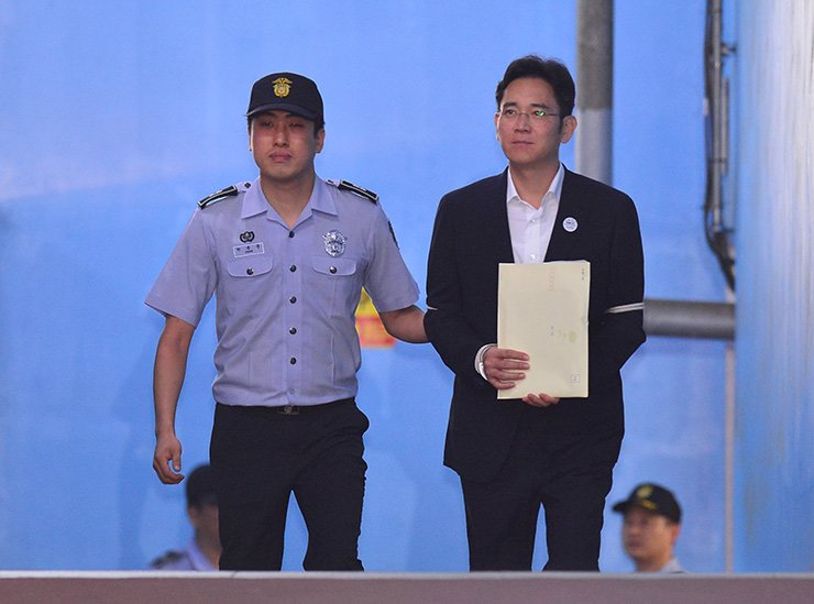 Lee Jae-yong, right, Samsung Electronics vice chairman, is escorted to a prison bus after attending his ruling trial at the Seoul Central District Court in Seoul, Friday. Lee was sentenced to five years in prison on multiple corruption charges, including bribery and embezzlement. / Yonhap