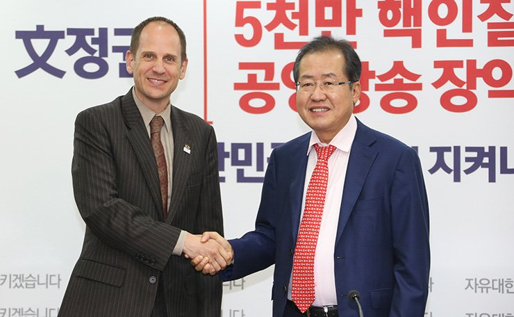 Canadian Ambassador Eric Walsh, left, shakes hands with the main opposition Liberty Korea Party Chairman Hong Joon-pyo at the party headquarters in Seoul, Sept. 14. The Canadian ambassador said his country supports the South Korean government's move to resolove the North Korea nuclear issue through diplomacy. / Yonhap