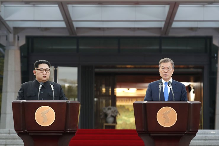 President Moon Jae-in speaks as North Korean leader Kim Jong-un listens during a joint announcement of agreements reached in a summit at Panmunjeom, Friday. / Joint Press Corps