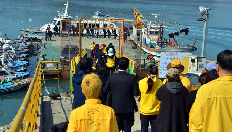 Bereaved family members walk toward the end of a dock to board a ship which will take them near the semisubmersible recovery ship carrying the ferry Sewol in Mokpo, South Jeolla Province, Sunday. / Yonhap