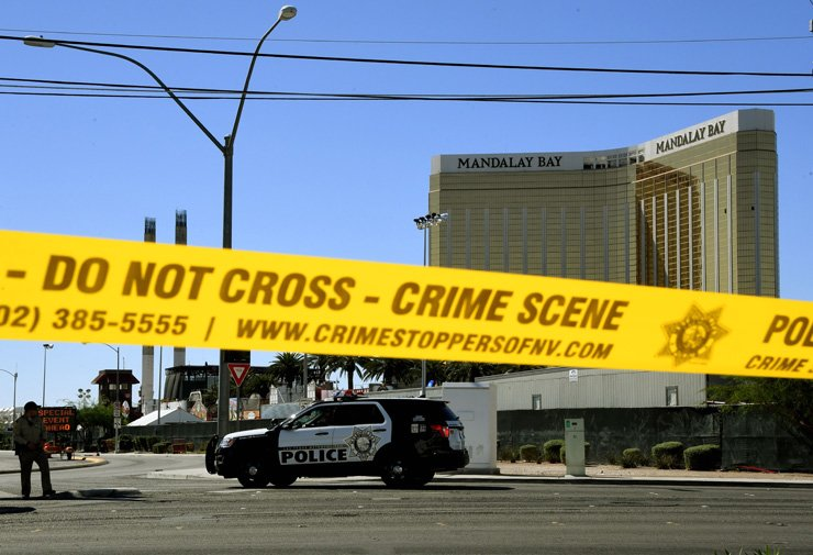 Crime scene tape surrounds the Mandalay Hotel (background with shooters window damage top right) after a gunman killed at least 58 people and wounded more than 500 others when he opened fire on a country music concert in Las Vegas, Nevada on October 2, 2017. Police said the gunman, a 64-year-old local resident named as Stephen Paddock, had been killed after a SWAT team responded to reports of multiple gunfire from the 32nd floor of the Mandalay Bay, a hotel-casino next to the concert venue. / AFP-Yonhap