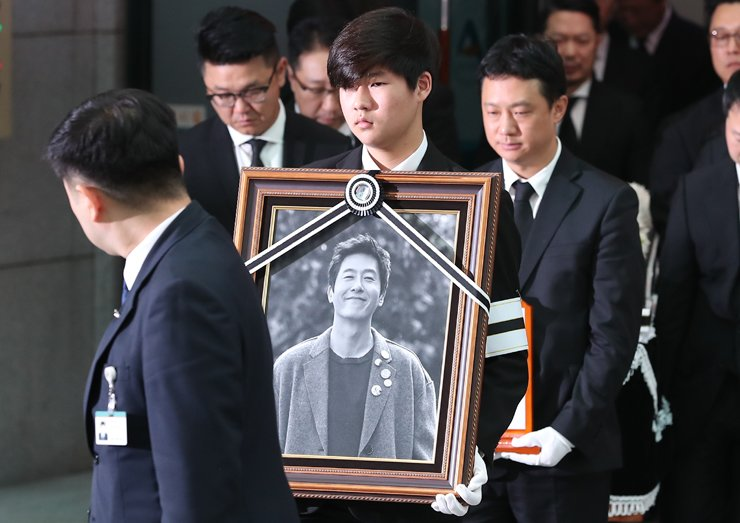 Members of the funeral procession for actor Kim Joo-hyuck carry his portrait and coffin from Asan Medical Center in Seoul on Thursday. / Yonhap