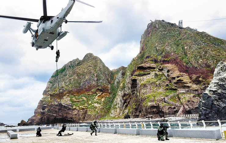 Navy's Underwater Demolition Team (UDT) agents are being released from an UH-60 helicopter over Dokdo, South Korea's eaternmost islets, in this 2013 file photo. / Korea Times file