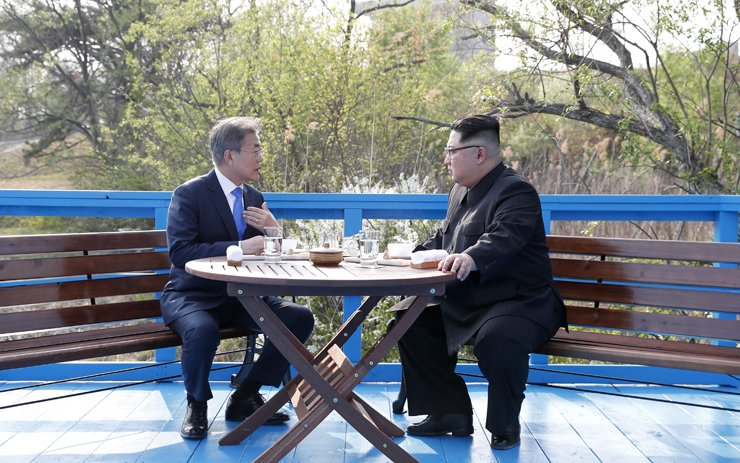 South Korean President Moon Jae-in talks with North Korean leader Kim Jong-un at a makeshift table on a wooden bridge during their summit meeting at the truce village of Panmunjeom, Friday, in this photo provided by Yonhap News TV. / Joint press corps