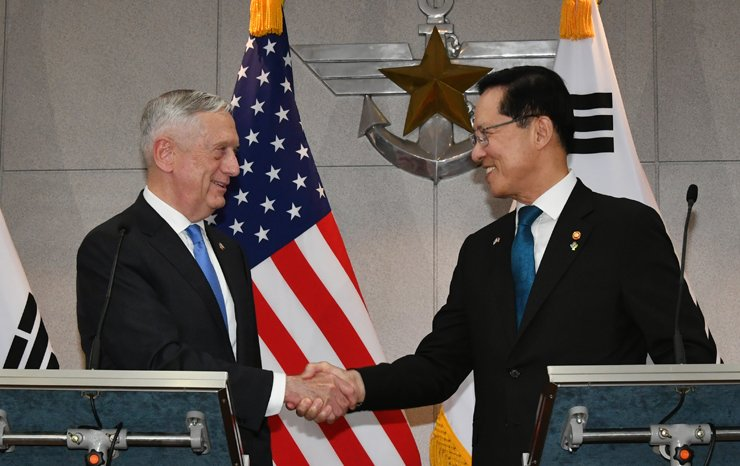 South Korean Defense Minister Song Young-moo, right, shakes hands with his U.S. counterpart James Mattis before holding talks at his office in Yongsan, Seoul, Thursday. They discussed a series of defense issues including follow-up measures to realize a peace agreement from the Washington-Pyongyang summit. / Yonhap