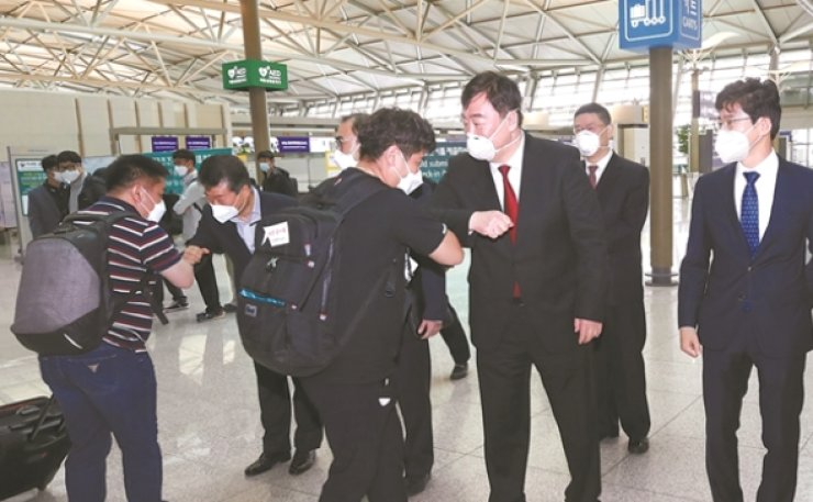 Chinese Ambassador to Korea Xing Haiming bumps elbow with one of the Korean businesspeople leaving for China as a new COVID-19 greeting at Incheon International Airport, May 10. Yonhap