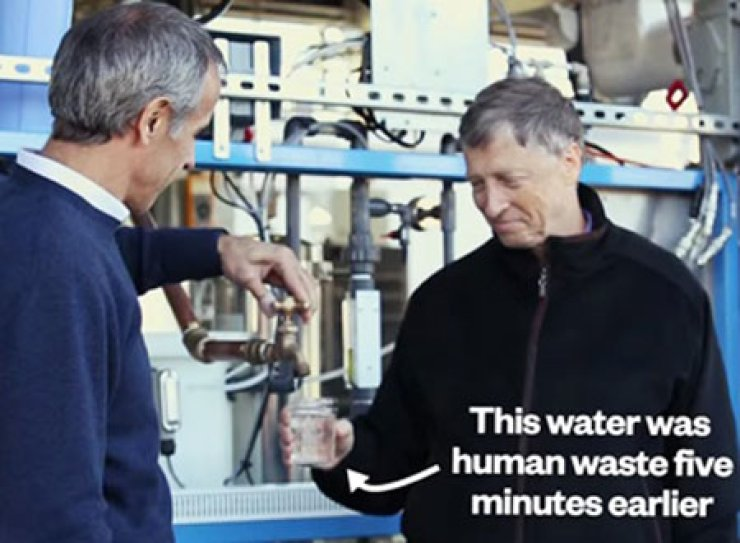 Microsoft co-founder Bill Gates, right, looks at a glass of water made from human waste. / YouTube screen capture
