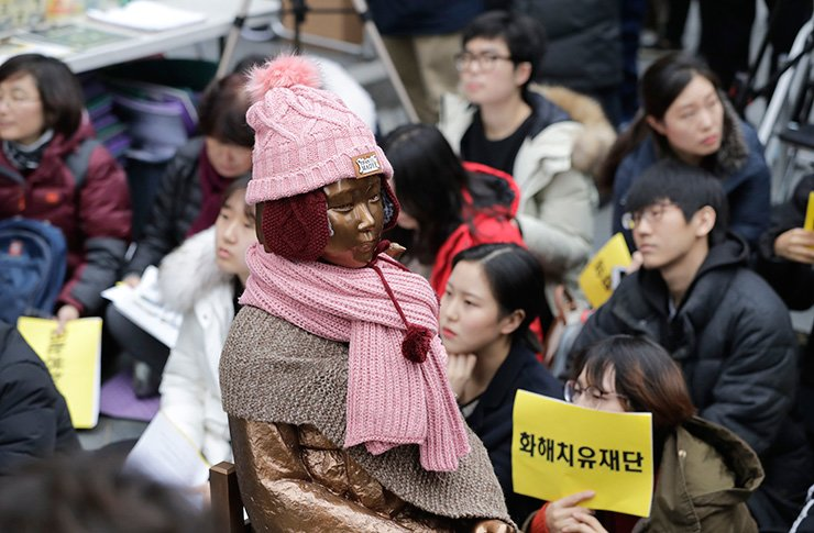 A statue of a girl representing thousands of Korean women enslaved for sex by Japan's imperial forces before and during World War II, is seen as participants hold signs reading 'Reconciliation and Healing Foundation' during a weekly rally against Japanese government near the Japanese Embassy in Seoul, Wednesday. Korea said Wednesday it will dissolve a foundation funded by Japan to compensate Korean women who were forced to work in Japan's World War II military brothels. AP
