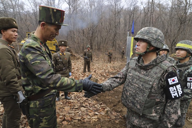 In this photo provided by South Korea's Defense Ministry on Thursday, a South Korean soldier, right, and North Korean soldier, left, shake hands as they meet to open a road connecting the two sides across the demilitarized zone in a project to excavate Korean War remains near the military demarcation line inside the Demilitarized Zone in Cheorwon, South Korea. Courtesy of South Korea's Defense Ministry