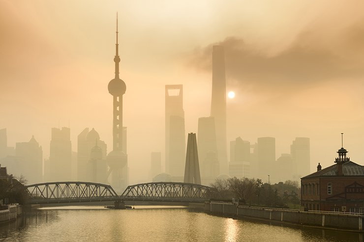Shanghai Financial Center and modern skyscraper city in misty gold lighting sunrise behind pollution haze, view from the bund in Shanghai, China. GettyimagesBank