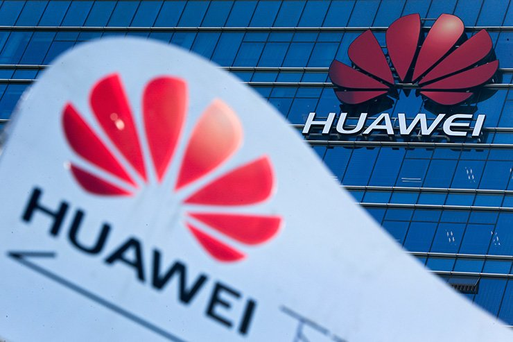 This Dec. 18, 2018, file photo shows company signage on display near the Huawei office building at its research and development center in Dongguan in south China's Guangdong province. A U.S. federal indictment accuses Huawei of stealing trade secrets from T-Mobile, in the form of a robot designed to automatically test phones for problems. AP