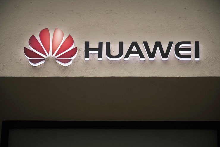 A picture taken on Feb. 4 shows the Huawei logo above the entrance of a Huawei store in Paris. Denmark has ordered the expulsion of two employees of the Chinese telecoms giant because their residence and work permits were not in order. AFP