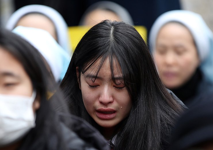 A rally participant sheds tears as she attends a weekly 'Wednesday demonstration' near a 'comfort woman' statue in front of the Japanese Embassy in Seoul, Wednesday. Yonhap