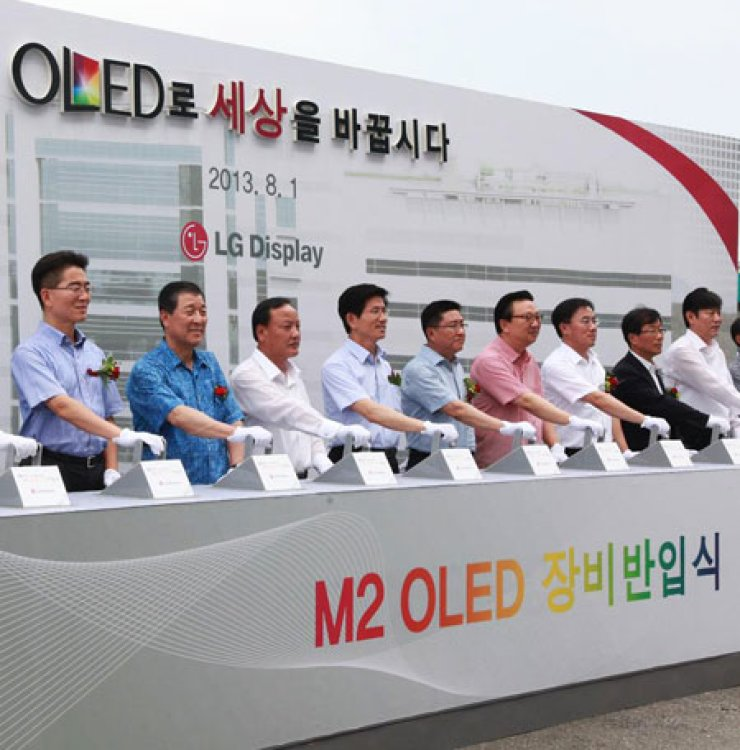 LG Display CEO Han Sang-beom, fifth from left, pulls a lever with Gyeonggi Province Governor Kim Moon-soo, fourth from left, and other LG executives and guests to celebrate the first installment of equipment to be used on a new OLED display-manufacturing line at the firm's display complex in Paju, Gyeonggi Province, Thursday. / Courtesy of LG Display