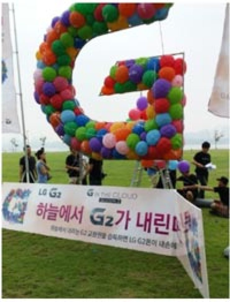 Balloons containing 100 free coupons for LG's latest GT smartphone are seen at a promotional event in a park in Seoul, Friday./ Captured from the Internet