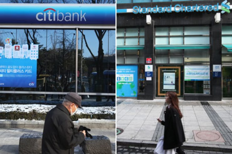 People walk by branches of Citibank Korea, left, and Standard Chartered Bank Korea in Seoul, Wednesday. The two banks are under investigation for a data leak of about 130,000 customers from branches in Changwon, South Gyeongsang Province, the largest ever information leak here. / Yonhap