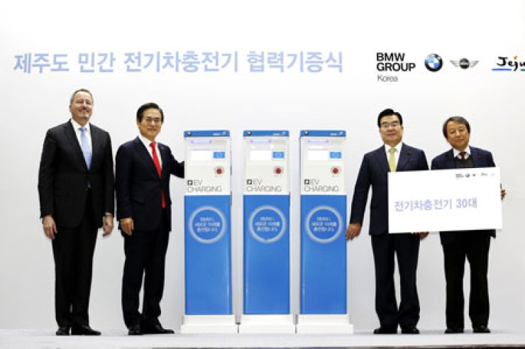 From left, Bill McAndrews, vice-president of BMW Group; Kim Hyo-joon, CEO of BMW Korea; Jeju Governor Woo Keun-min; and Kim Dae-hwan, CEO of Jeju Electric Vehicle Service, pose during a donation ceremony at the office of the Jeju Special Self-Governing Province, Tuesday. BMW donated 30 charging stations for electric vehicles to Jeju Island. / Courtesy of BMW Korea