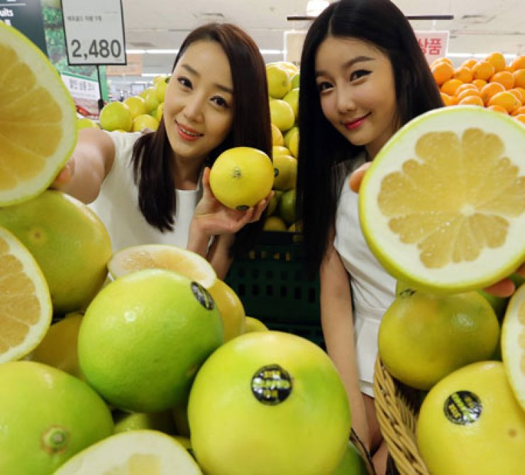 Models pose with 'melogold' grapefruit from the United States at the Yongsan outlet of e-mart, Seoul, Monday. The nation's largest retail supermarket chain said the melogold grapefruit is a hybrid of a grapefruit and an orange./ Yonhap