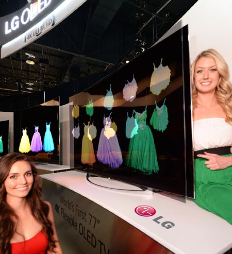 Models pose with LG Electronics' flexible OLED TV, at this year's International Consumer Electronics Show (ICES) in Las Vegas, Tuesday (KST). / Courtesy of LG Electronics