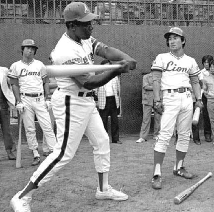 Hank Aaron, center, provides batting tips to Samsung Lions players during a visit to Korea in 1982.