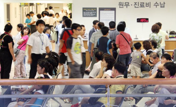 Patients and their families are packed into a lobby at a hospital in Seoul, waiting to make appointments with doctors. Clinics have been banned from collecting resident registration numbers from patients since Thursday when the Personal Information Protection Law went into effect. But hospitals continue to illegally gather the numbers. / Korea Times file