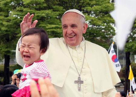 The Pope is in full regalia with his pastoral staff during the Mass of Assumption of Mary. / Joint Press Corp, AP-Yonhap and YonhapThe Pope is officiating the Mass.The crucifix carried in procession by prelatesDaejeon World Cup Stadium is filled to capacity.A closer look at the participants and a crying baby