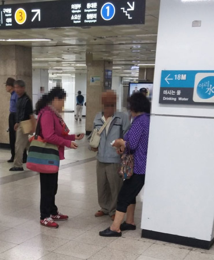 Two 'Bacchus women' are seen attempting to sell counterfeit Viagrapills to an elderly man at Jongno 3-ga Station in central Seoul. / Korea Times