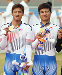 Kim jong-gyu, back, and Jeon Dae-hong, race during the men's individual cycling event at the Incheon Asia Para Games, Sunday. They won Korea's first gold medal of the Games. / Yonhap