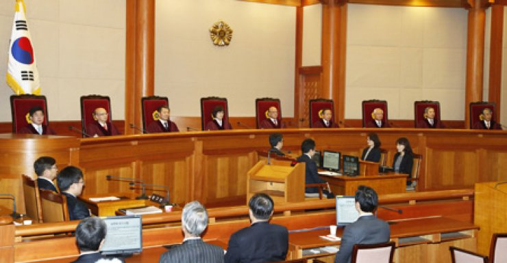 Nine Constitutional Court justices are seated during a verdict on the United Progressive Party, Friday. From left are Seo Ki-seog, Ahn Chang-ho, Lee Jin-sung, Lee Jung-mi, Park Han-chul, the chief justice, Kim Yi-su, Kim Chang-jong, Kang Il-won and Cho Yong-ho. Only judge Kim Yi-su voted in favor of the UPP. / Yonhap