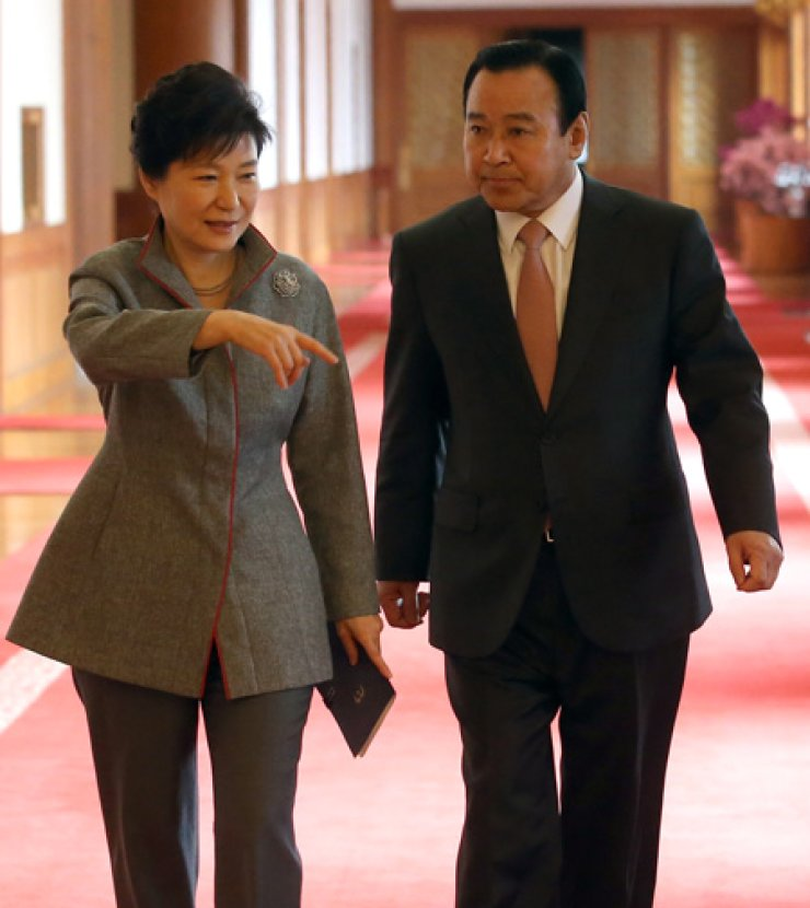 President Park Geun-hye and new Prime Minister Lee Wan-koo talk while walking to attend a Cabinet meeting at Cheong Wa Dae, Tuesday. / Yonhap
