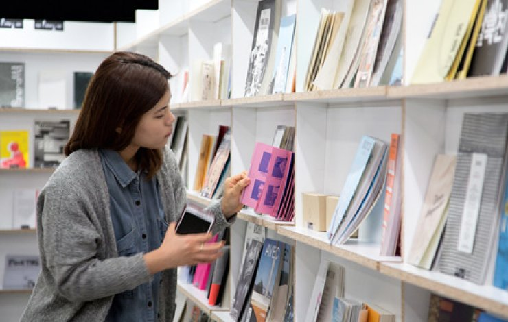A visitor to the 'Public Library Independent Publishing Reading Room' exhibit reads independently published books at the National Library of Korea in southern Seoul. / Courtesy of National Library of Korea