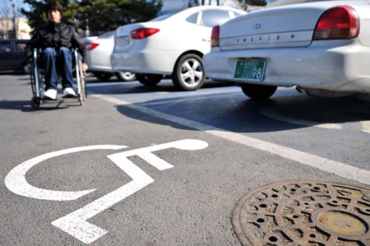 A man in a wheelchair approaches a parking zone for the disabled. / Korea Times file