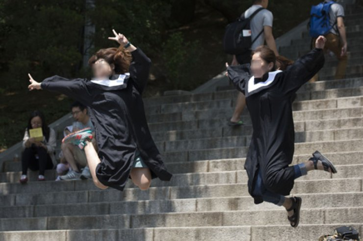 Chinese tourists jump for a photograph on Ewha Womans University campus in Seoul, Monday. / Korea Times photo by Choi Won-suk