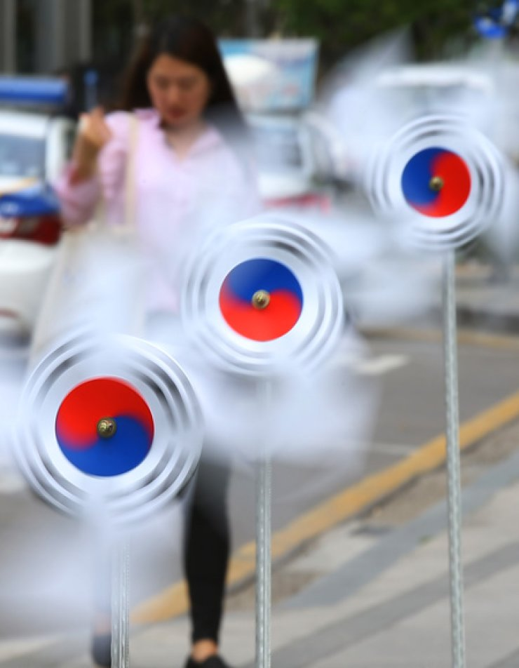 Pinwheels patterned with the 'taegeuk,' a symbol on the Korean flag, whirl near the National Museum of Korean Contemporary History in central Seoul, Friday. They were installed ahead of the 70th anniversary of Liberation Day, which falls on Aug. 15. / Yonhap