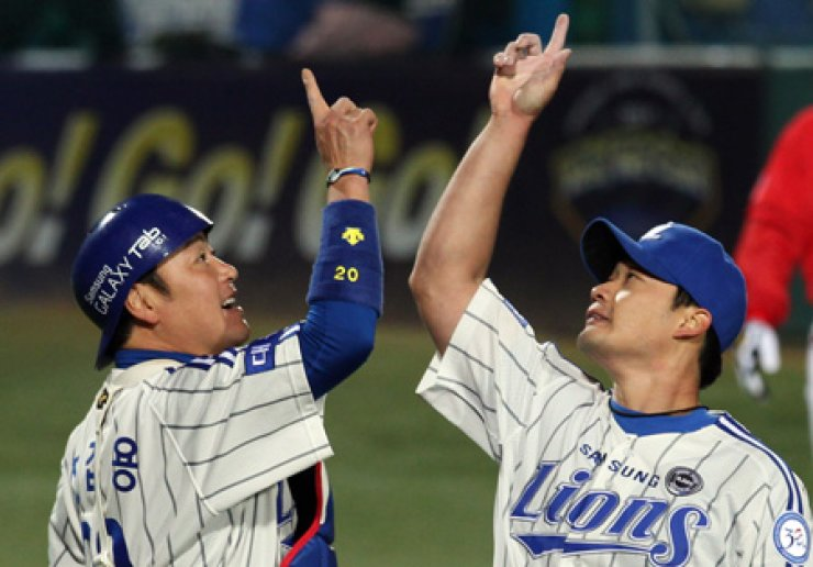 Samsung Lions catcher Jin Kab-yong, left, celebrates with teammate Oh Seung-hwan (now at Japan's Hanshin Tigers) after a 2-1 victory over SK Wyverns in the game two of the 2011 Korean Series in Daegu in this Oct. 26, 2011, photo. / Korea Times file