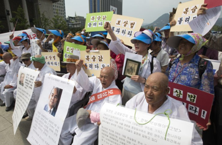 Bereaved family members of Koreans, who died while undertaking forced labor overseas during Japan's colonial rule, call on the government to establish a law offering them compensation during a rally at Gwanghwamun Square in Seoul, Friday. / Yonhap