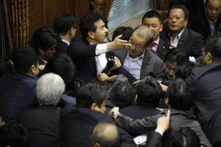 Japanese lawmakers scuffle during a committee voting of security bills at the upper house in Tokyo, Thursday. Japan's ruling Liberal Democratic Party (LDP) pushed contentious security bills through a legislative committee, catching the opposition by surprise and causing chaos in the chamber. If the vote stands, the legislation will go to the upper house of parliament for final approval. The lawmaker at center left, is LDP's Masahisa Sato, acting chairperson of the committee. /AP-Yonhap