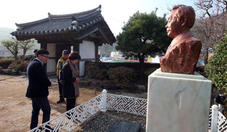 People pay their respects to former President Kim Young-sam, who passed away early Sunday, in front of a bust set up at Kim's birth house in Geoje, South Gyeongsang Province, Sunday. / Yonhap